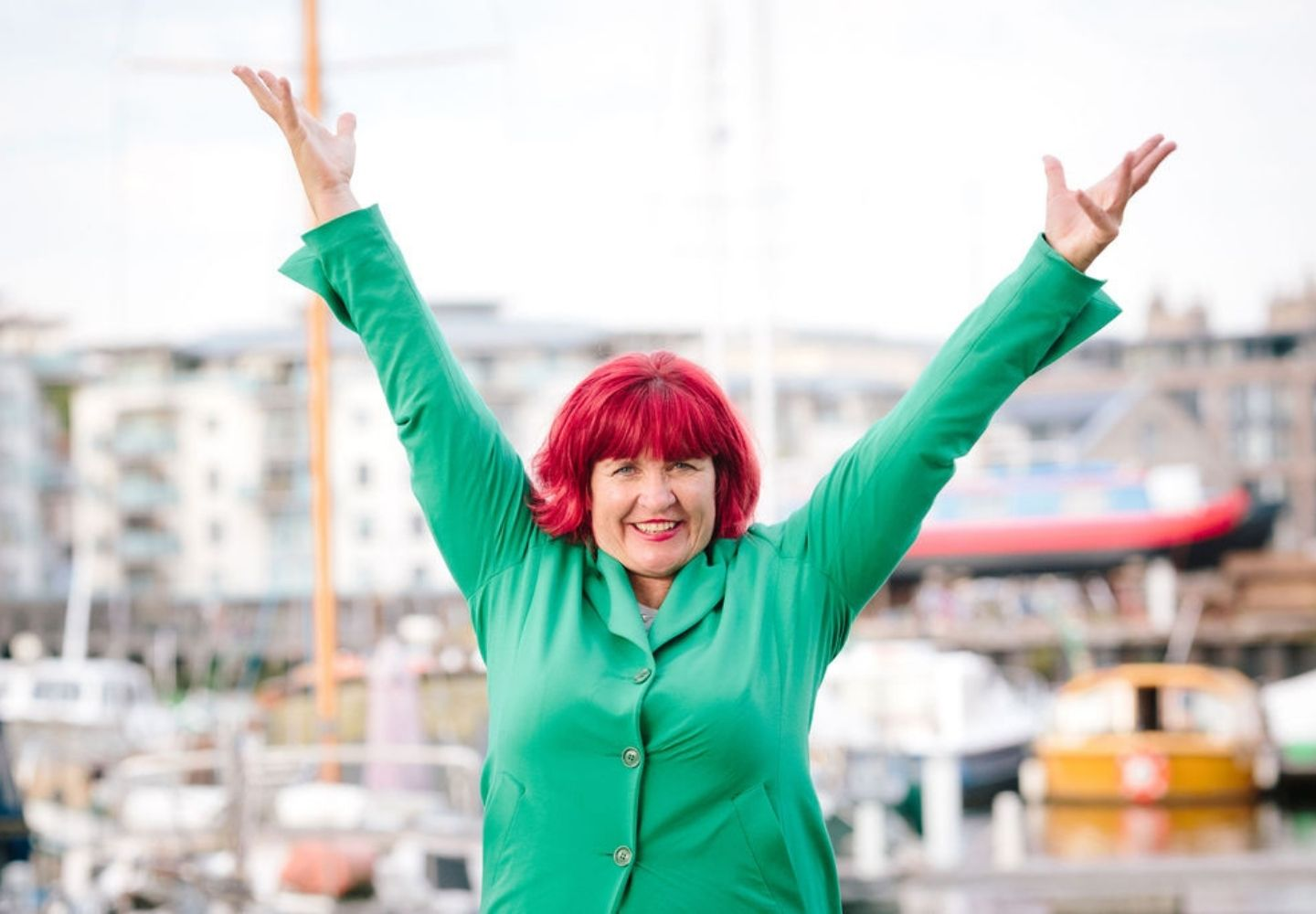 Traci with arms in the air in front of Bristol Harbour